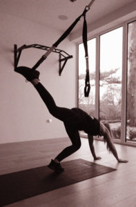 "see how the TRX is around her ankle in this photo? The next move is to kick the other foot up to ""meet it."""